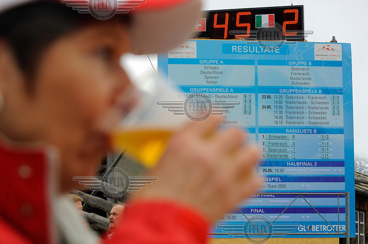A Swiss supporter drinks a beer by the scoreboard at the other official Euro 2008 football tournament: the European Championship of Mountain Villages. The tournament was held at the summer training ground of hosts FC Gspon, standing at 2008 metres above sea-level,  and surrounded by 4000 metre alpine peaks. It is the highest football pitch in Europe, and reachable only by cable car, or a long walk. Amateur league teams from eight countries took part.