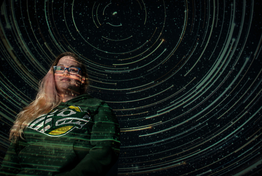Natural Sciences Major Angela Cook, photographed in UAA's Planetarium and Visualization Theater. Cook was recently awarded an Alaska Space Grant Research Fellowship for her undergraduate research which focuses on modeling supermassive black holes at the center of galaxies.