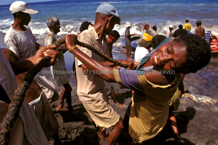 Lamalera, Indonesia..Villagers join togther to drag slices of blubber, some weighing over 100 kg, up the beach at Lamalera...Photograph by Stuart Isett.©2003 Stuart Isett