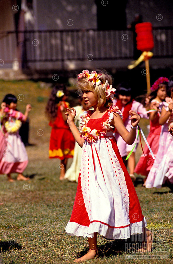 A young schoolgirl wearing a plumeria lei and traditional aloha wear dances in the May Day festivities at Lili'oukalani School in Kaimuki, Oahu.
