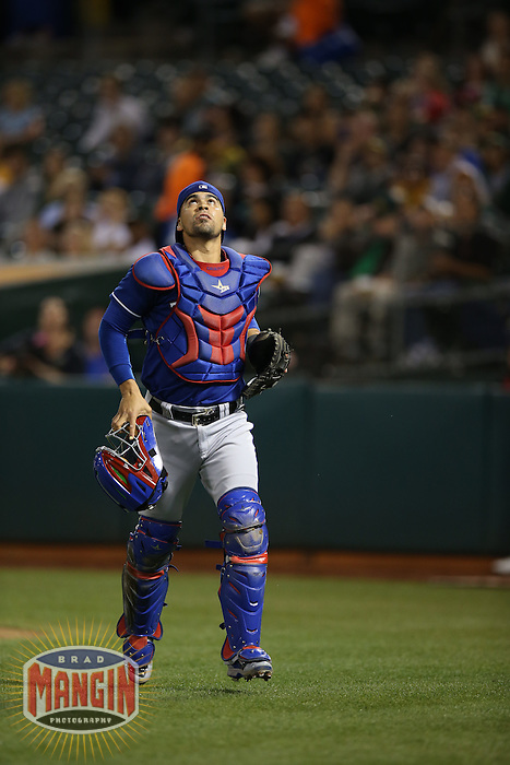 OAKLAND, CA - SEPTEMBER 17:  Robinson Chirinos #61 of the Texas Rangers chases a foul ball against the Oakland Athletics during the game at O.co Coliseum on Wednesday, September 17, 2014 in Oakland, California. Photo by Brad Mangin