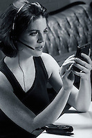 A young woman talking on a telephone headset and working with a Palm Pilot.