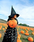 USA, California, young girl dressed as a witch holding a pumpkin at Bob's Pumpkin Patch, Half Moon Bay