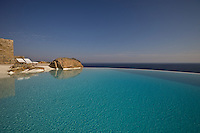 A pair of sun-loungers beside the crystal clear water of the infinity pool overlooking the Aegean sea