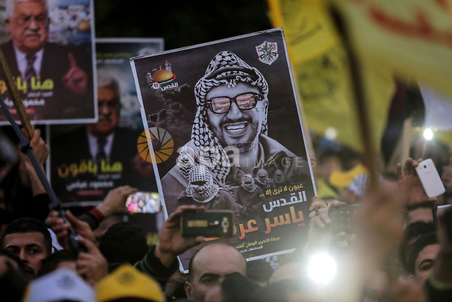 Supporters of the Fatah movement hold up a portrait of late Palestinian leader Yasser Arafat during a rally in Gaza City on December 31, 2017, marking the 53rd anniversary of the creation of the political party. Photo by Mohammed Dahman