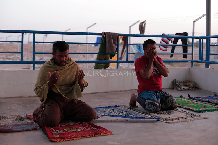 10/10/2014 -- Kirkuk, Iraq -- Two Bangladeshi workers pray after work in the garage were they live in Kornish street in the centre of Kirkuk.