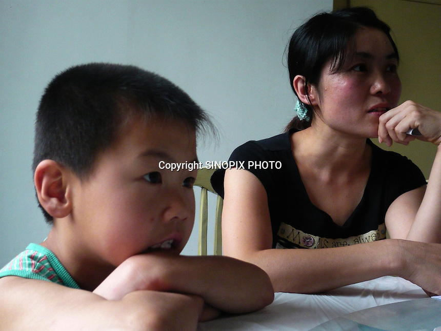 "Mrs Tian and her son Li Zhao Tian, 7 who suffers from blood cancer.  Xiditou village is known as one of China's worse ""cancer villages"" where a reported ten percent have died from cancer."