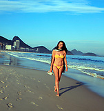 BRAZIL, Rio de Janiero, a woman takes a walk down the beach at Copacabana Beach