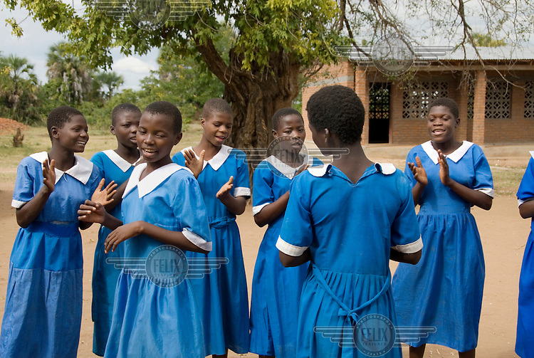 Girls clap their hands and sing at Namiyala school.