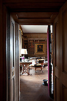 Portraits of the Bunbury family are framed by the oak bookcases in the library