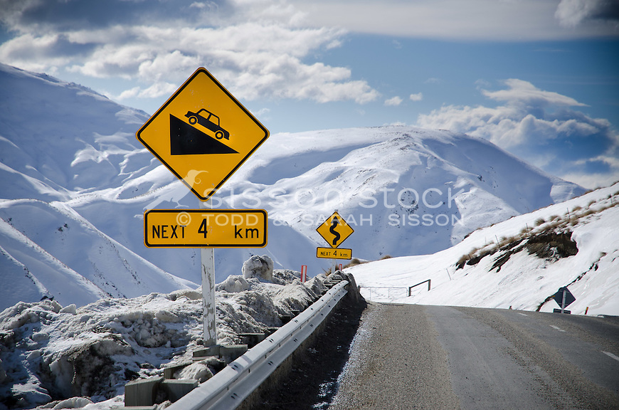 Close up picture of Steep grade and winding road signs on the treacherous Crown Range road between Queenstown and Wanaka. Winter time, snow and grit on road,  Sunny day looking down Cardona valley.