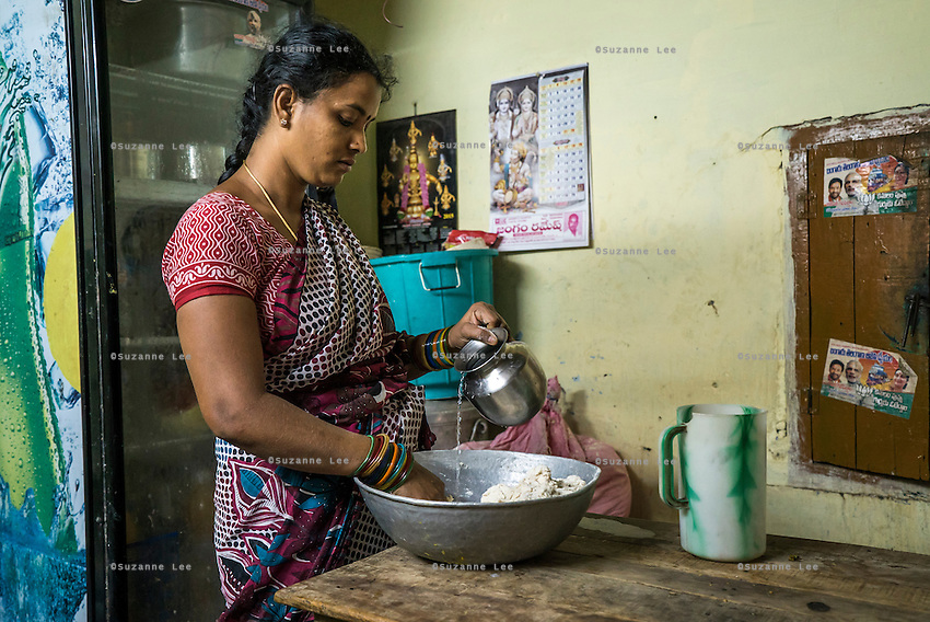 Lavanya Gattu, 32, a food stall operator, uses iJal water as she kneads dough in preparation for her day of business in Peddapur, a remote village in Warangal, Telangana, India, on 22nd March 2015. Lavanya buys iJal water and uses it for all her family consumption, and also cooks with it in her stall and serves it for free to customers who come to eat there. She leaves the iJal water cans at the door, showing off to her customers that she uses safe water. Photo by Suzanne Lee/Panos Pictures for Safe Water Network