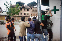 Srinagar, India-August 8, 2010: Kashmiri teenagers retreat and hide behind a wall after throwing rocks at Indian police and military in downtown Srinagar