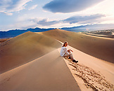 USA, California, young woman sitting on sand dune, Stovepipe Wells, Death Valley National Park