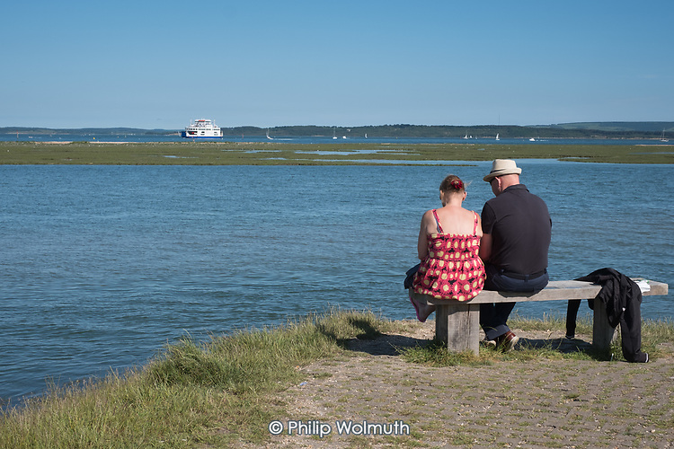Man and woman sitting on a bench overlooking the Solent and the sle of Wight, Lymington, Hampshire.