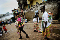 Marbella Slum, Freetown, Sierra Leone - women walking the street near the health centre