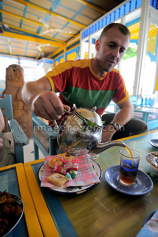 Africa, Tunisia, Nabeul. Tourist Frank enjoying a tea and some biscuits in a typical local tunisian coffee shop. --- No releases available, but releases may not be needed for certain uses. --- Info: Image belongs to a series of photographs taken on a journey to southern Tunisia in North Africa in October 2010. The trip was undertaken by 10 people driving 5 historic Series Land Rover vehicles from the 1960's and 1970's. Most of the journey's time was spent in the Sahara desert, especially in the area around Douz, Tembaine, Ksar Ghilane on the eastern edge of the Grand Erg Oriental.