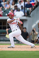 Yosvani Alarcon Tardio (11) of the Cuban National Team follows through on his swing against the US Collegiate National Team at BB&T BallPark on July 4, 2015 in Charlotte, North Carolina.  The United State Collegiate National Team defeated the Cuban National Team 11-1.  (Brian Westerholt/Four Seam Images)