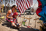 Christine and Casen Bayea pay their respects to friends Andrew Ashcraft and Clayton Whitted two of the 19 Granite Mountain Hotshots who perished in the Yarnell Fire at a makeshift memorial outside Fire Station 7 in Prescott, Arizona, July 2, 2013.