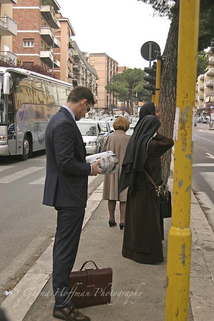 Business man, nuns, woman waiting at a Rome bus stop.