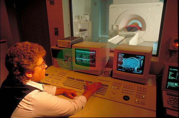 technician using computer reading MRI scan in progress