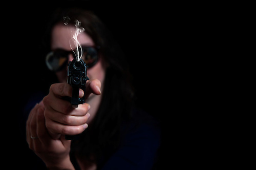 Female with a pistol shot in studio.