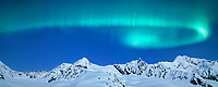 Aurora borealis swirls across sky over the Alaska mountain range on the Canwell Glacier, Alaska.