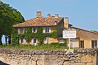 A white sign saying Clos Fourtet 1er premier first Grand Cru Classe and the chateau building itself and vineyard behind a stone wall Saint Emilion Bordeaux Gironde Aquitaine France