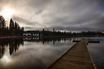 Idaho, North, Kootenai County, Rose Lake. A wooden dock on calm water on a January morning.
