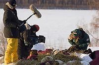 Film crew photographs vet Caroline Griffits working on dog @ Ruby Chkpt 2006 Iditarod Alaska Winter
