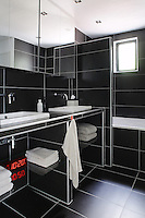 Interior designer Pascal Angelis has created the illusion of a spacious bathroom with the clever implementation of black tiles on floor and walls