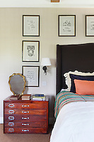 An old plan chest makes a practical bedside table and chest of drawers in this bedroom