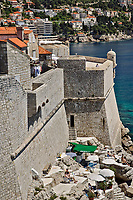 Tourists sunning and outdoor cafe outside the city wall around Old Town Dubrovnik a UNESCO World Heritage Site, Croatia.