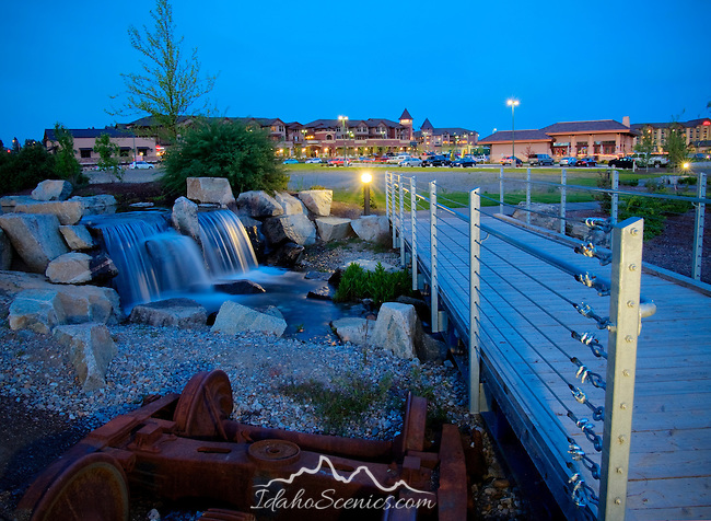 Idaho, North, Kootenai County, Coeur d'Alene. The walking path around Riverstone pond crosses a manmade creek beside a water feature with Riverstone Village distant.