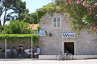A bar cafe restaurant called Wind in the harbour, with people sitting outside in the shade drinking. Luka Gruz harbour. Dubrovnik, new city. Dalmatian Coast, Croatia, Europe.