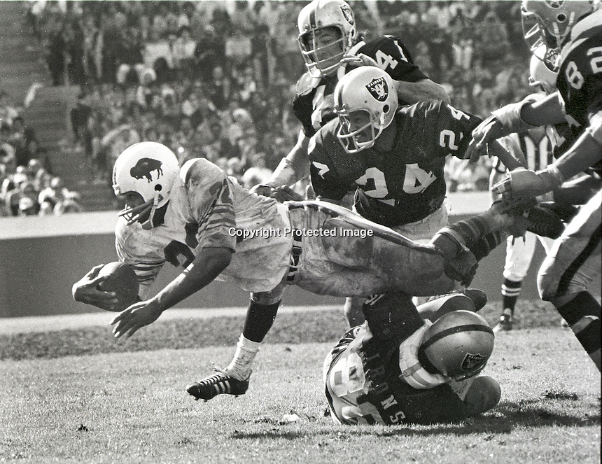 Buffalo Bill's running back O.J. Simpson is stopped by.Oakland Raider's Gerald Irons, Willie Brown #24, and Phil Villapiano. 1972 photo/Ron Riesterer
