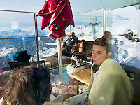 "Switzerland. Canton Valais. Tourists seat on a restaurant terrace in Verbier at "" Les Ruinettes"" ( 2200 meters). Verbier is a village located in the municipality of Bagnes in the Val de Bagnes. Verbier is one of the largest holiday resort and ski areas in the Swiss Alps. Sunny day. Cable car. 3.01.2012 © 2012 Didier Ruef"