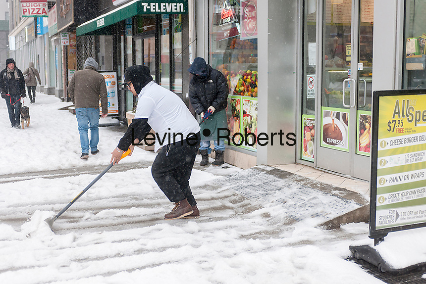 Workers shovel snow in the Chelsea neighborhood of New York on Tuesday, March 14, 2017. Originally predicted as a blizzard with up to 20 inches of snow the storm has changed its course and only 4 to 6 inches of snow, sleet and rain are expected, accompanied by howling winds of course. (© Richard B. Levine)