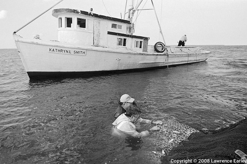 Two long-haul fishermen are removing fish from a net in Core Sound.  Long-haul fishing is an old method of catching fish that is similar to haul-seining.  The runboat in the background belongs to the Luther Smith Seafood Co. in Atlantic and will take the fish back to the fish house for sorting, packing and selling.