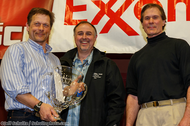 David Booker and Dr. Stuart Nelson DVM award the Alaska Airlines Leonhard Seppala Humanitarian Award to Martin Buser at the musher 's finishers banquet in Nome on Sunday March 16 after the 2014 Iditarod Sled Dog Race.<br /> <br /> PHOTO (c) BY JEFF SCHULTZ/IditarodPhotos.com -- REPRODUCTION PROHIBITED WITHOUT PERMISSION