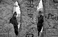 BERLINO / GERMANIA - 10 NOVEMBRE 1989.DUE GUARDIE DI CONFINE DELLA DDR (VOPOS) GUARDANO ATTRAVERSO IL MURO NEI PRESSI DELLA POTSDAMER PLATZ..FOTO LIVIO SENIGALLIESI..BERLIN / GERMANY - 10 NOVEMBER 1989.THE WALL ON THE WESTERN SIDE NEAR POTSDAMER PLATZ..PHOTO BY LIVIO SENIGALLIESI