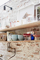 In the kitchen, wooden shelving is fitted to an exposed brick façade, which has been painted to look old and adds an industrial vibe to the kitchen.