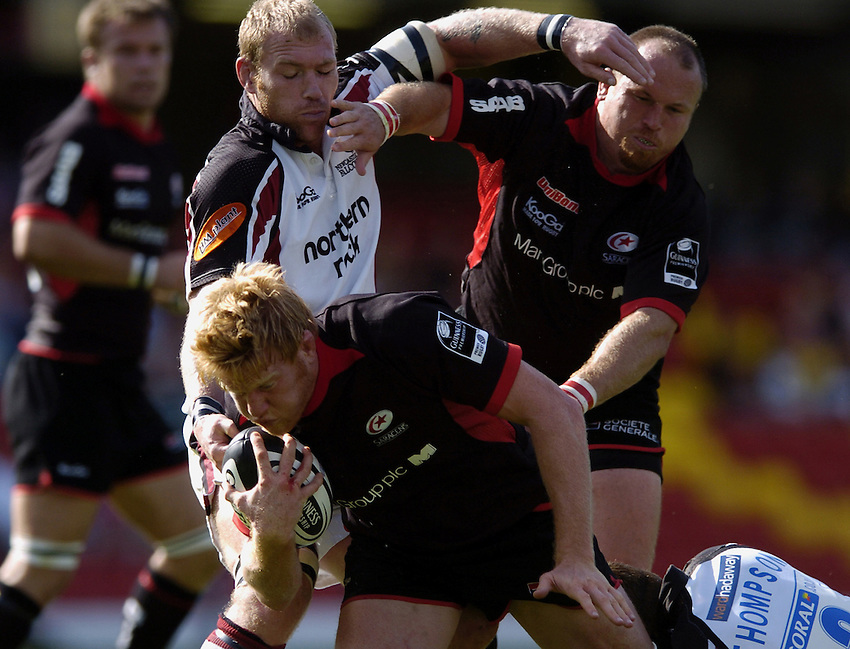 Photo: Jonathan Butler..Saracens v Newcastle Falcons. Guinness Premiership. 17/09/2006..Hugh Vyvyan (bottom) of Saracens is tackled by Matt Thompson (L) of Newcastle.