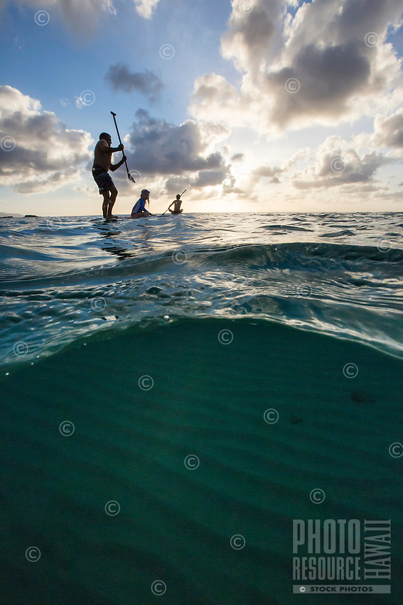 A family standup paddles in Waimea Bay at sunset