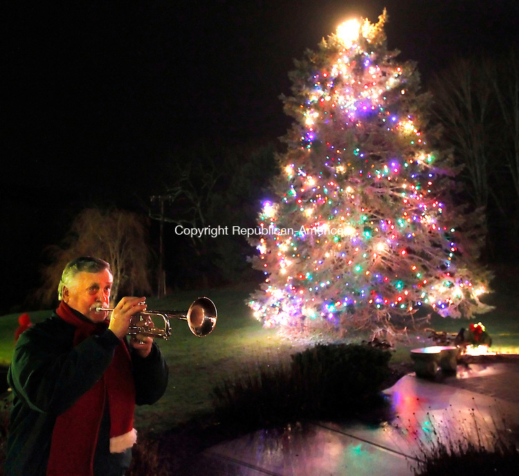 "Oxford, CT-07 December 2012-120712CM07-   Art Hlywa, of Oxford, plays Christmas music with his trumpet during the lighting of the Christmas tree Friday night  at the Stephen B. Church Memorial Town Hall in Oxford.  Hlywa said he's been playing music for tree lighting since 2004.  He added it's unfortunate it rained during the ceremony, but added, ""It didn't dampen the spirits of the people here.""  Christopher Massa Republican-American"