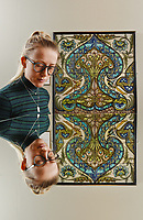 BNPS.co.uk (01202 558833)<br /> Pic: ZcharyCulpin/BNPS<br /> <br /> Pictured: Emma Rowland from the Russell-Coates Art Gallery with a Floral Ogee tile panel. De Morgan created an almost perfectly symmetrical panel apart from the two birds below the centre of the panel. The panel is reflected in a mirror.<br /> <br /> 'Sublime Symmetry' at the Russell-Coates Art Gallery and Museum in Bournemouth, Dorset<br /> <br /> The Sublime Symmetry exhibition showcases the work of William De Morgan. The celebrated Arts and Crafts designer (1939-1917) was seen as the most inventive ceramic designer of the Victorian period.  The exhibition which runs until the 2nd February explores the Mathematics behind De Morgan's Ceramic designs.