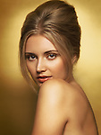 Sensual beauty portrait of young glamorous woman with beautiful hairstyle in golden colors on gold background
