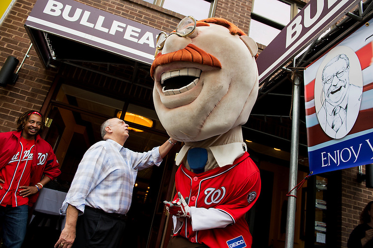 "UNITED STATES - OCTOBER 02:  Anthony Harris, owner of Bullfeathers restaurant, greets Teddy of the Washington Nationals racing presidents during a ""Teddy Wins! "" rally on Capitol Hill, as Terrance Briscoe, of the Nat Pack, looks on.  Teddy has never won a race, which is run every home game.  Bullfeathers is themed in honor of President Theodore Roosevelt. (Photo By Tom Williams/CQ Roll Call)"