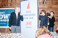 Press photographers take pictures as Republican presidential candidate and former Florida governor Jeb Bush speaks to a crowd in the barn of Dr. and Mrs. James Betti in Rye, New Hampshire, for former Massachusetts senator Scott Brown's No B.S. BBQ series.