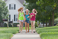 Three Young Girls Walking together in a  Residential Neighborhood.